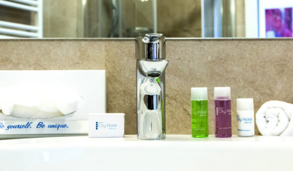 City Hotel Merano, suite. Bathroom in natural stone with amenities, hair dryer and wellness bag for SPA and gym. ©Anguane
