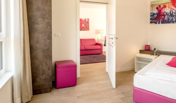 City Hotel Merano, City 3-room suite. Plenty of space for families or people with a desire for freedom. Modern design. Bedroom, living room (with double bed sofa) and single room with tiled floor. Air conditioning and underfloor heating. Non-smoking suite. Daily housekeeping. ©Florian Busch