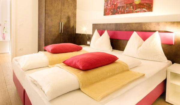 City Hotel Merano, City-suite trilocale. Camera da letto con colori vivaci, letto kingsize e tapparelle. Non-fumatori e anallergico. ©Florian Busch