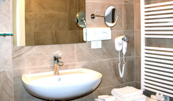 City Hotel Merano, bathroom in natural stone with hair dryer, mak-up mirror and amenities. Furthermore wellness bag with bathrobe, slippers and sauna towel for free use of SPA and gym ©Anguane