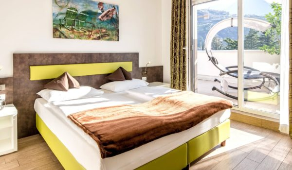 City Hotel Merano, Panoramic Suite (43-53m²). Modern design and a calming silence on the 5th floor. Generous suite with air conditioning, king-size bed or two single beds, WIFI Internet for free and underfloor heating. All rooms are allergy-friendly and non-smoking rooms. Spacious terrace with view on the surrounding Merano mountains. ©Florian Busch
