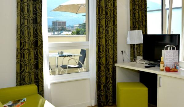 City Hotel Meran Panorama Suite. Über den Dächern von Meran. Ruhig mit herrlichem Blick auf die Berge. Weitläufige Terrasse mit Liegen, Sonnenschirm und Sitzecke. ©demipress