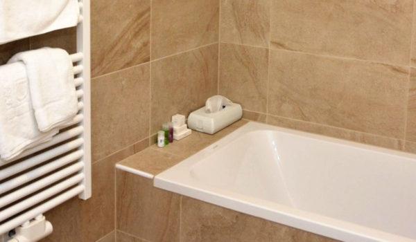 City Hotel Merano, la nostra suite più grande dispone di due bagni in pietra naturale con doccia, WC, bidet, inoltre una vasca da bagno. Borsa wellness, prodotti di cortesia specchio per il trucco e asciugacapelli per la vostra comodità. Riscaldamento a pavimento per un maggior comfort abitativo. ©Demipress