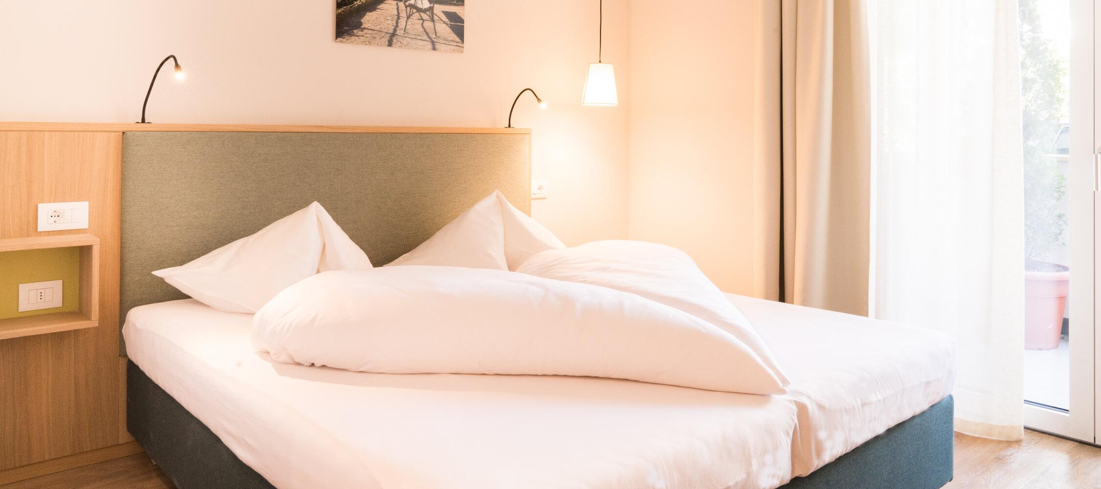 Hotel_Flora_Merano_Rooms_Komfort_Doppelzimmer_Olivia_Bett_DSC01114_BeatricePilotto_2250x1000